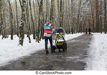 Woman walking with baby stroller in winter park. People