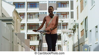 Woman walking with bicycle in city street 4k - Happy woman...