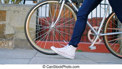 Woman walking with bicycle in city street 4k - Low section...