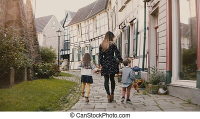 Woman walking with boy and girl, holding hands. Mother, two...