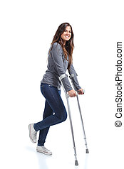 Woman walking with crutches on a white isolated background...