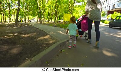 Woman walking with daughter and baby carriage - Young female...