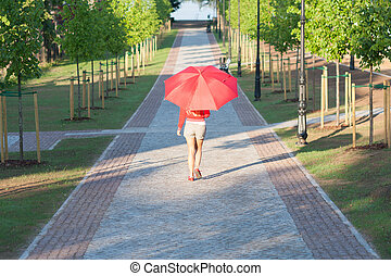 Woman walking with red umbrella on sunny morning