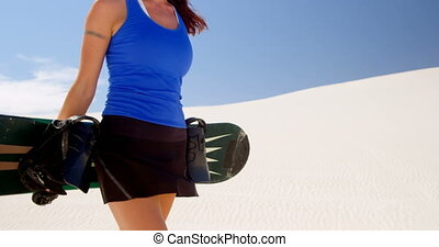 Woman walking with sand board in the desert 4k - Beautiful...