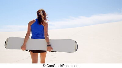 Woman walking with sand board in the desert 4k - Rear view...