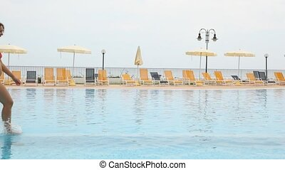Woman walks along pool in front of chaise longue and beach umbrella