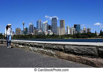 Woman walks along Sydney skyline