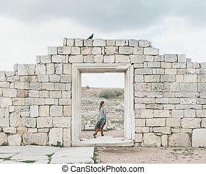 Woman walks among the ancient ruins.