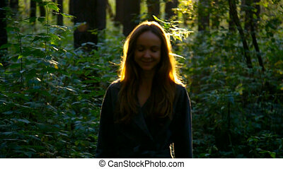 woman walks and long flowing hair shines in back sun -...