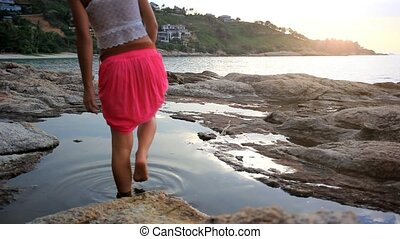 Woman walks at sunset rocky beach in the sea. Koh Samui....