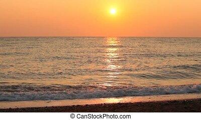 Woman walks barefoot along rolling waves on beach -...