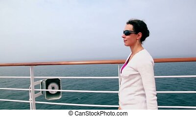 Woman walks by deck near fence and watch seascape during cruise