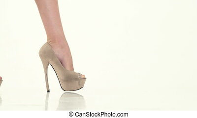 woman walks in beige shoes on high heel on white background