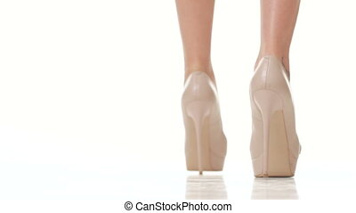 woman walks in beige shoes on high heel on white background...