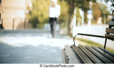 Woman walks in the defocused are go into focus zone sits down on bench uses smartphone reads text