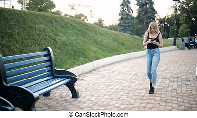 Woman walks in the park looks into smartphone feels discomfort of her feet stops sits down on bench