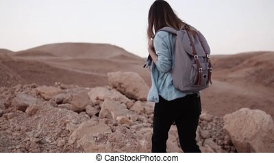 Woman walks near mountain drop. Slow motion. Young tourist...