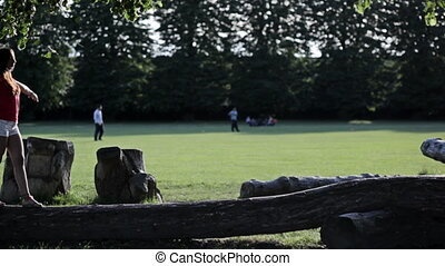 Woman walks on a log in a park