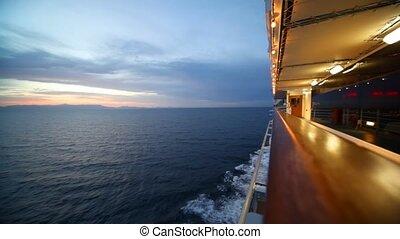 woman walks on illuminated deck of cruise ship