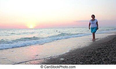 Woman walks on the beach at sunset