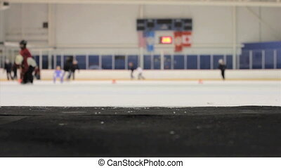 Woman Walks Onto Ice At Ice Rink - A young woman carefully...