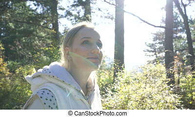 woman walks through the forest on a sunny day, portrait