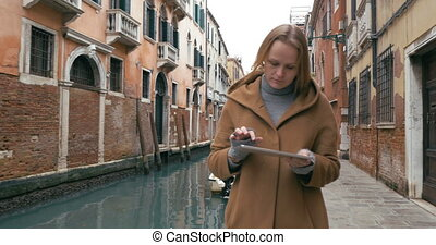 Woman wandering in Venice with pad - Steadicam shot of a...