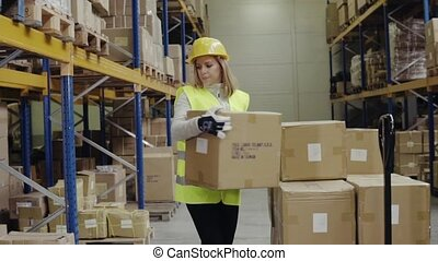 Woman warehouse worker unloading boxes. - Young woman...