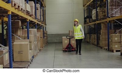 Woman warehouse worker with hand forklift truck. - Young...