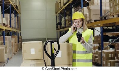 Woman warehouse worker with smartphone. - Young female...