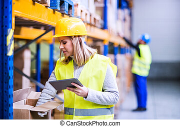 Woman warehouse worker with tablet.