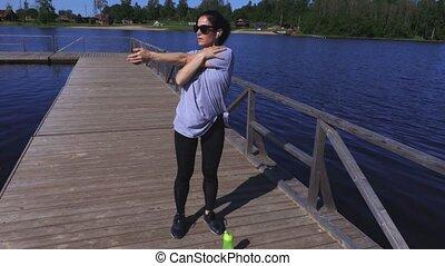 Woman warm up before workout at park near lake