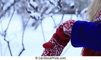 Woman warming frozen hands in mittens