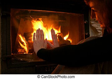Woman warming hand at fireplace