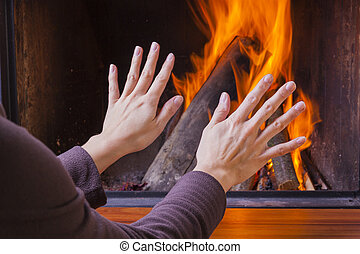 woman warming hands at fireplace
