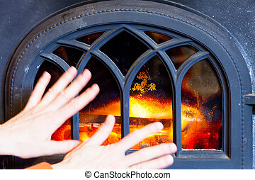 Woman warming her hands at fire fireplace interior. Heating.