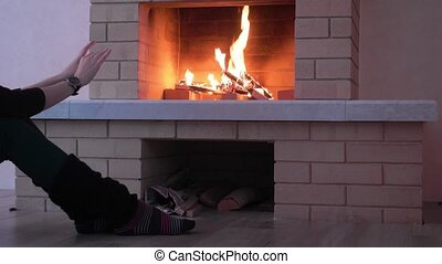 Woman warming her hands at fire fireplace.