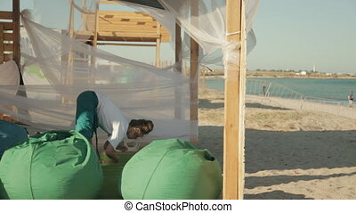 Woman warming up before a yoga class near the sea in windy...