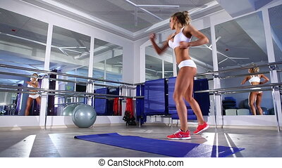 Woman  warming up for exercising in a gym