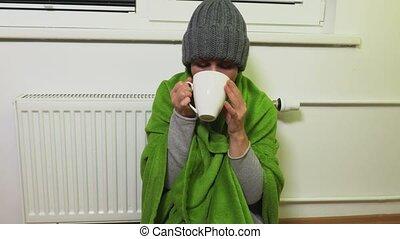 Woman warms near heating radiator and drink tea