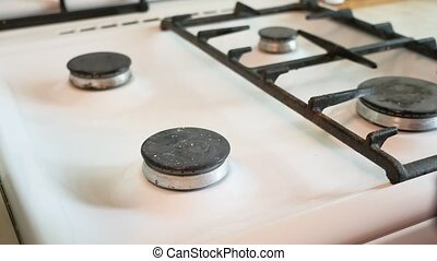 woman washes a gas stove in the kitchen cleaning