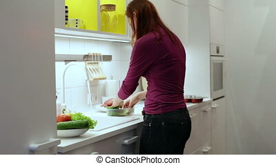 Woman washes a green onions in the sink