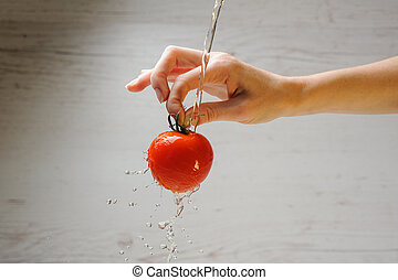 Woman washes a tomato