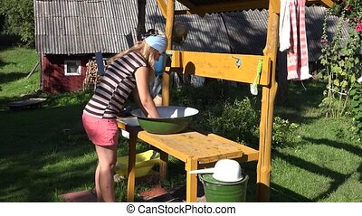 woman washes clothes in bowlin yard. Daily routine country.