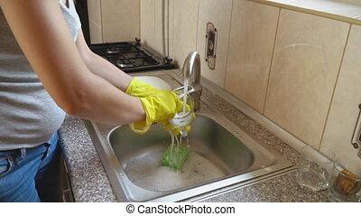 Woman washes dishes - woman washes dishes in a sink