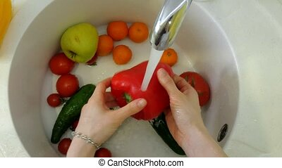 Woman washes fresh vegetables under the tap in the sink in...