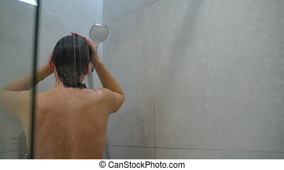 Woman washes her hair, shoulders, arms and back in the shower. Hair care, beauty and wellbeing concept. Slow motion