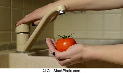 woman washes her hands tomatoes - Picture of a woman opens a...