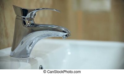 woman washes her hands under bathroom tap Closeup - woman...