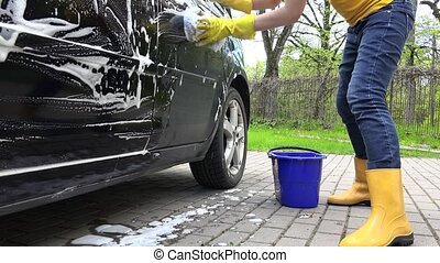 Woman washing automobile in open air. Handheld shot. - Woman...
